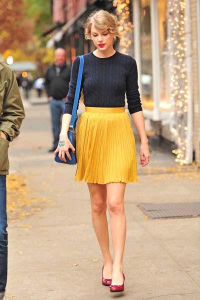 Casual ντύσιμο με μπλε πουλοβεράκι, κίτρινη πλισέ κοντή φούστα, κόκκινα παπούτσια και μπλε τσάντα