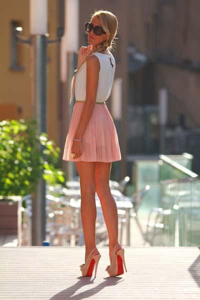 Μίνι ροζ φούστα πλισέ με λευκό τοπ και nude ψηλοτάκουνες γόβες
