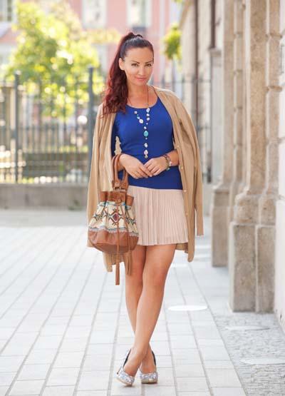 Κοντή μπεζ φούστα πλισέ με μπλε μπλούζα, μπεζ ζακέτα, γόβες και έθνικ τσάντα