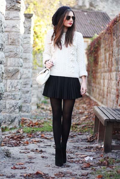 Χειμωνιάτικο σύνολο με μαύρη πλισέ μίνι φούστα, πουλόβερ, μαύρο καλσόν, άσπρη τσάντα και μαύρο μποτάκι μέχρι τον αστράγαλο