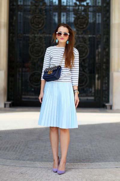 Άσπρη μακρυμάνικη μπλούζα με οριζόντια λεπτή μαύρη ρίγα, μίντι γαλάζια φούστα μέχρι το γόνατο, μωβ γόβες και μπλε τσαντάκι