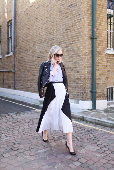 Ροκ chic ντύσιμο με δερμάτινο biker jacket, γαλάζιο πουκάμισο, ασπρόμαυρη μίντι φούστα από πλισέ ύφασμα και μαύρες γόβες