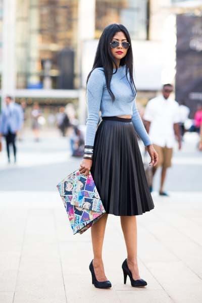 Σαγηνευτικό θηλυκό ντύσιμο με γαλάζιο μακρυμάνικο crop top, μαύρη δερμάτινη πλισέ μίντι φούστα, μαύρη γόβα και τσάντα φάκελο με cartoon prints