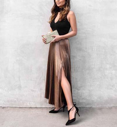 Chic ντύσιμο για γάμο με μαύρο τοπ με V λαιμόκοψη, τσάντα φάκελο σε χρυσό χρώμα, μπρονζέ μακριά φούστα πλισέ με σκίσιμο και μαύρες γόβες