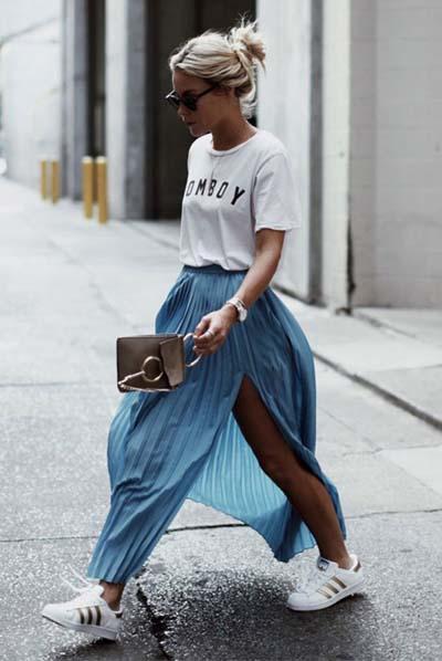 Street style ντύσιμο με λευκό t-shirt, πλισέ μακριά φούστα σε γαλάζιο χρώμα με σκίσιμο στο πλάι, sneakers και μικρό καφέ τσαντάκι