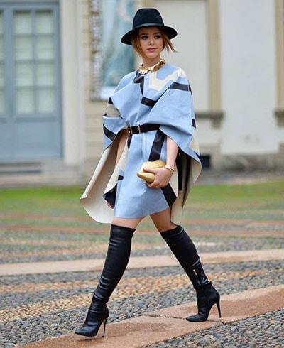 Κομψό μακρύ πόντσο πάνω από σύνολο με φούστα