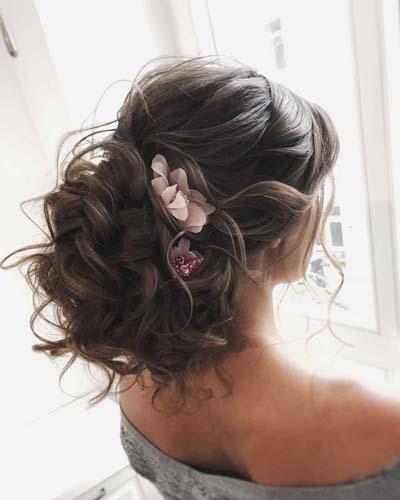 Ανάλαφρος χαμηλός κότσος σινιόν για νύφη διακοσμημένος με λουλούδια