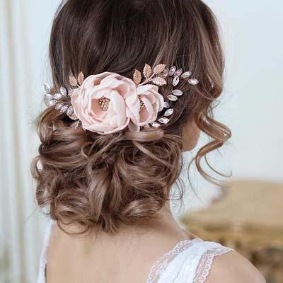 Χαμηλός ανάλαφρος κότσος για γάμο με μπούκλες και αξεσουάρ με λουλούδια - στρας