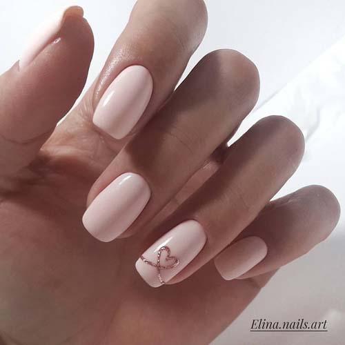 Απαλό ροζ χρώμα στα νύχια με διακριτικό σχέδιο καρδιάς