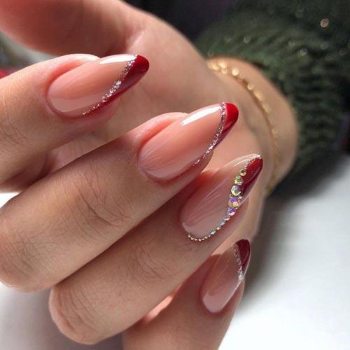 Κόκκινο ασύμμετρο γαλλικό σχέδια στα νύχια με στρας