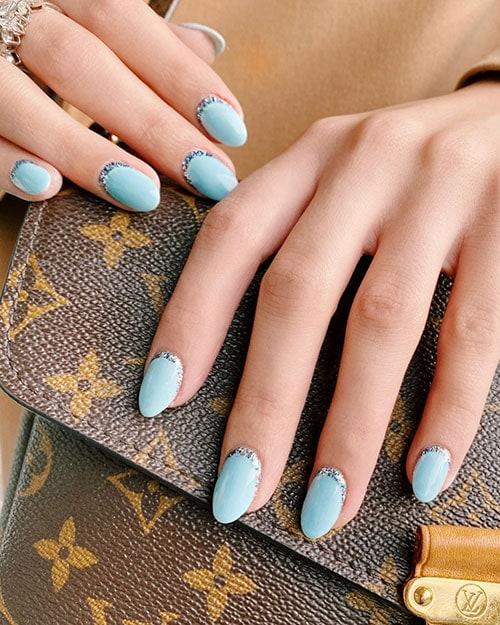 Γαλάζια νύχια με λεπτή γραμμή glitter στη ρίζα