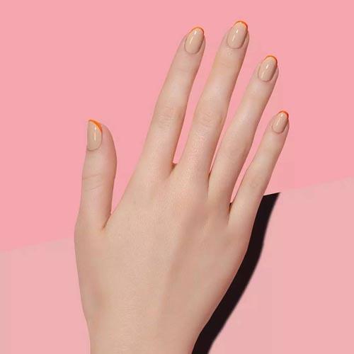 Οβάλ nude νύχια με λεπτή πορτοκαλί γραμμή γαλλικού